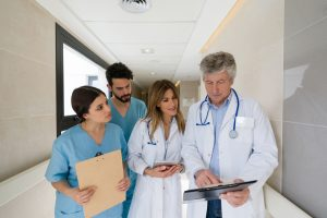 Senior doctor talking to his team of interns while pointing something on clipboard at the hospital  - healthcare concepts